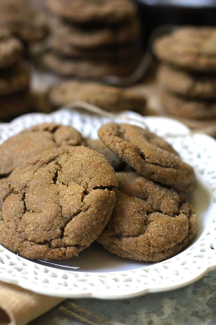 Side what of gingersnap cookies on a white plate, with stacks of cookies in the background.