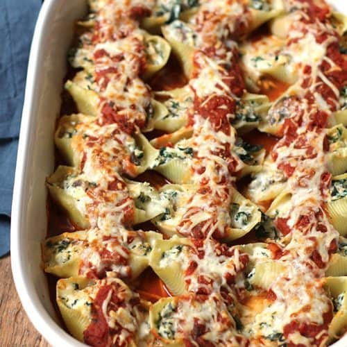 Side shot of a casserole dish of turkey sausage and spinach stuffed shells, with pasta sauce on top.