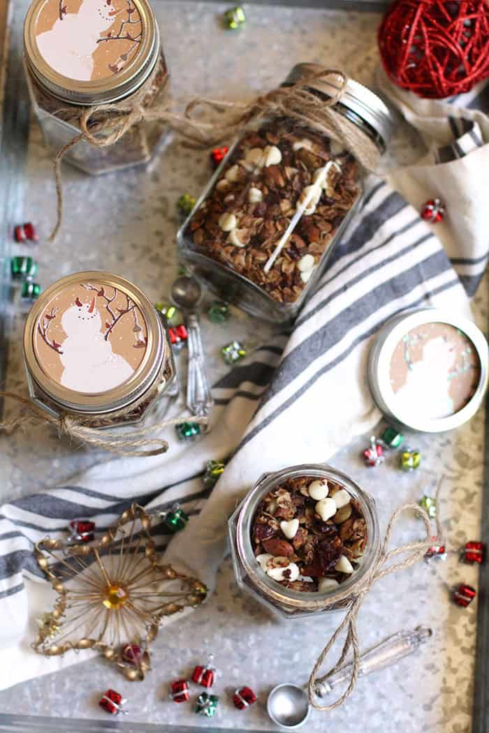 Overhead shots of white chocolate gingerbread granola in mason jars decorated for Christmas gifts.