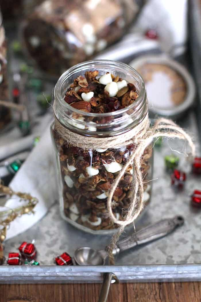 Shot of a mason jar without a lid, filled with gingerbread granola, on a gray tray.