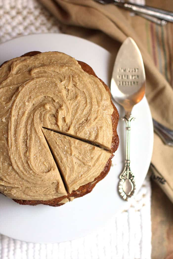 Overhead shot of banana layer cake with caramel frosting, with one piece cut, on a white cake plate with a silver spatula.