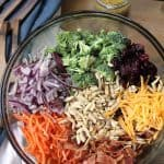 Broccoli Salad with Honey Dijon Dressing is bursting with color and nutrients. Eight cups of broccoli, with handfuls of carrots, onion, cheddar cheese, Raisins, bacon, and slivered almonds - all mixed together and topped with a delicious and tangy honey dijon dressing! | suebeehomemaker.com