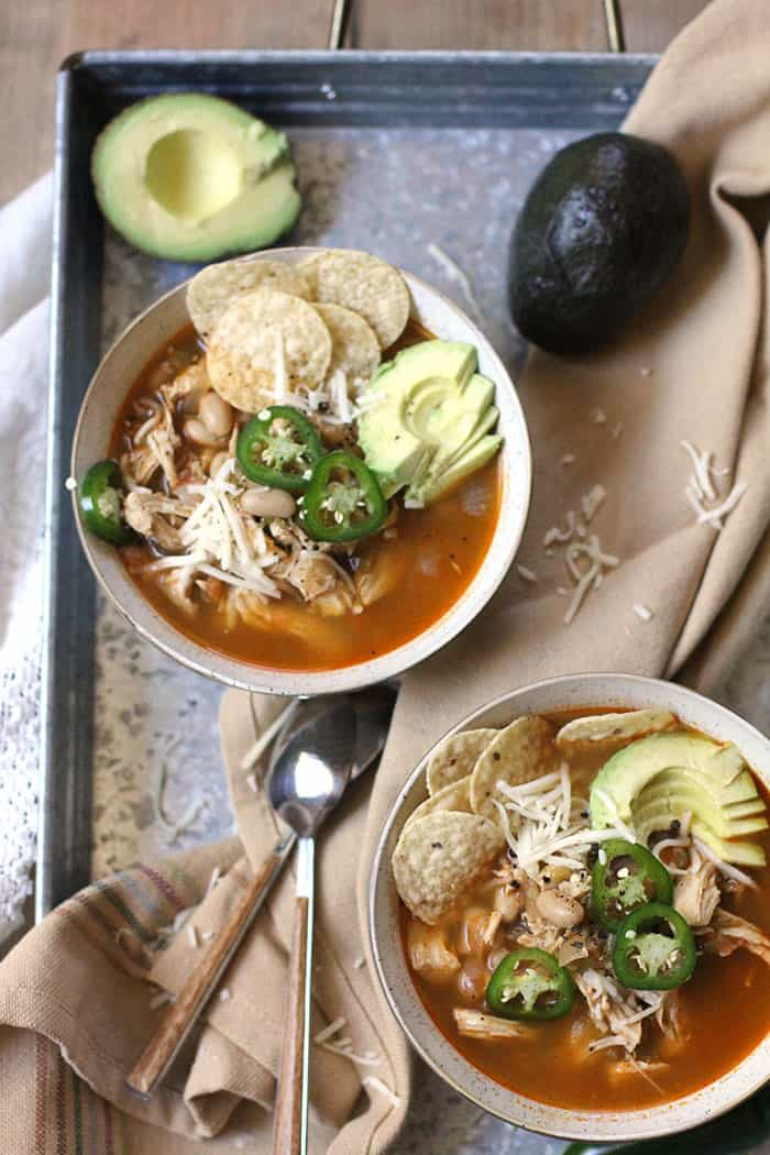 Overhead shot of two bowls of chicken chili, filled with toppings on a gray tray with a tan napkin, spoons, and avocado.