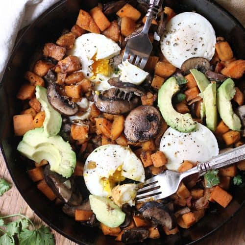Overhead shot of a large cast iron skillet filled with sweet potato breakfast hash, and two forks.