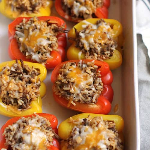 Side shot of a casserole dish of Mexican Beef Stuffed Peppers, with cheese on top.