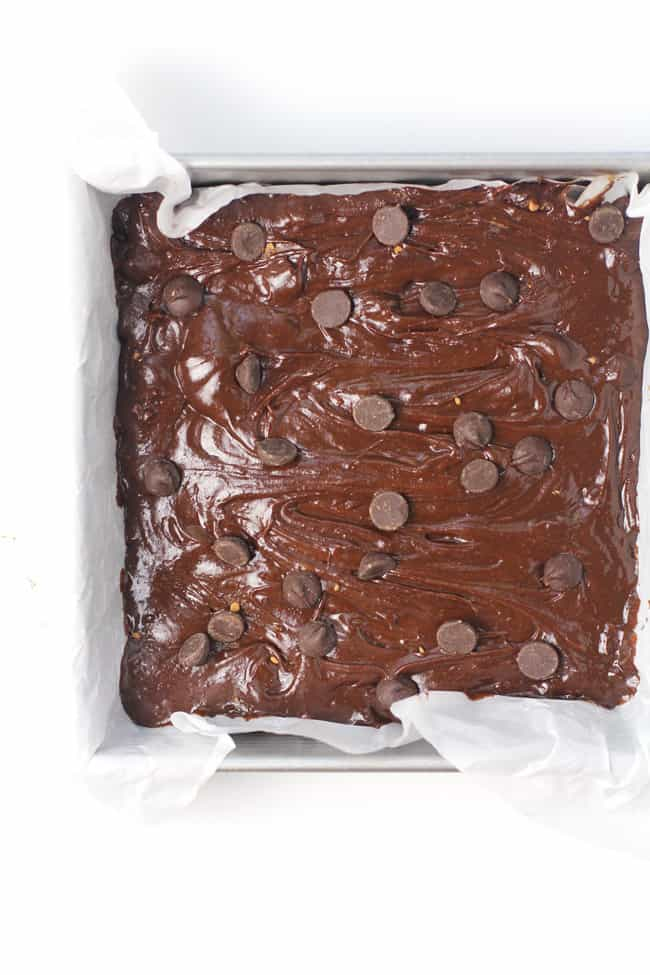 Overhead shot of an 8x8 pan of chocolate brownies, prepared with parchment paper.