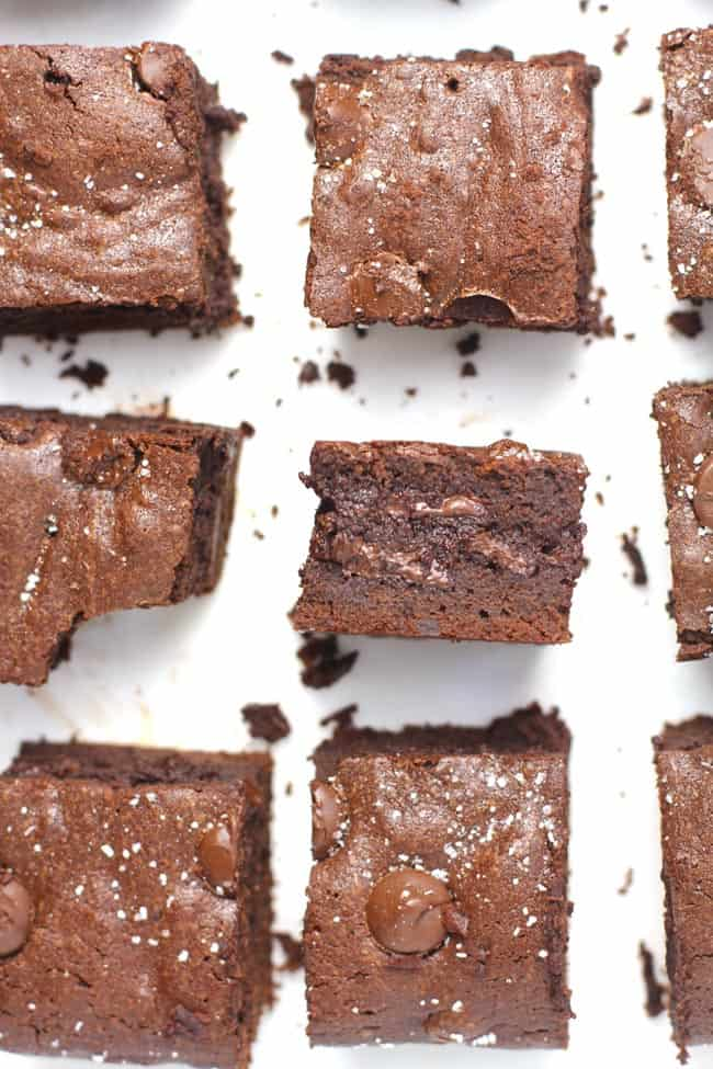 Overhead shot of sliced chocolate brownies, with one brownie on its side, showing its thickness.