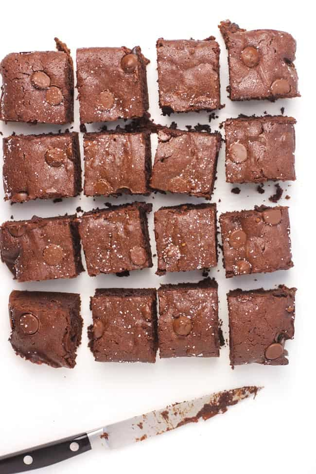 16 sliced brownies on a white background, with a knife.