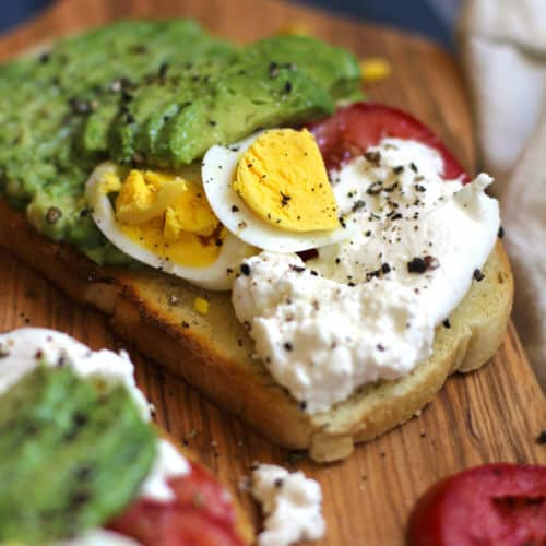 Side view of a piece of toast with burrata cheese, tomato, hard boiled egg, and avocado slices.