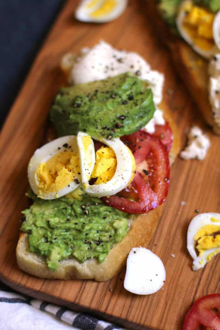 Overhead shot of some burrata avocado toast on a wooden board.