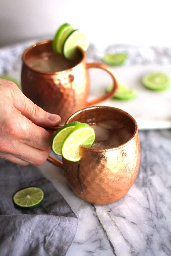 Side shot of a hand on a copper mug with Moscow mule.