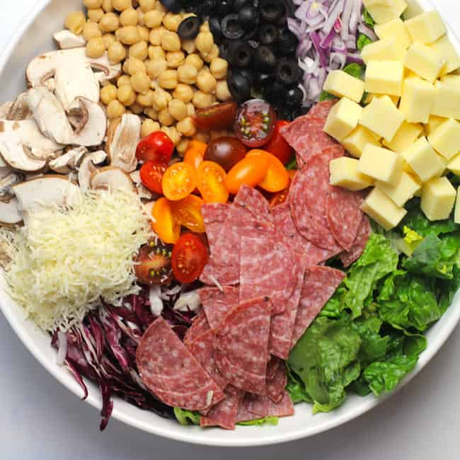 Overhead shot of a large white bowl of Italian Chopped Salad, separated by ingredient.