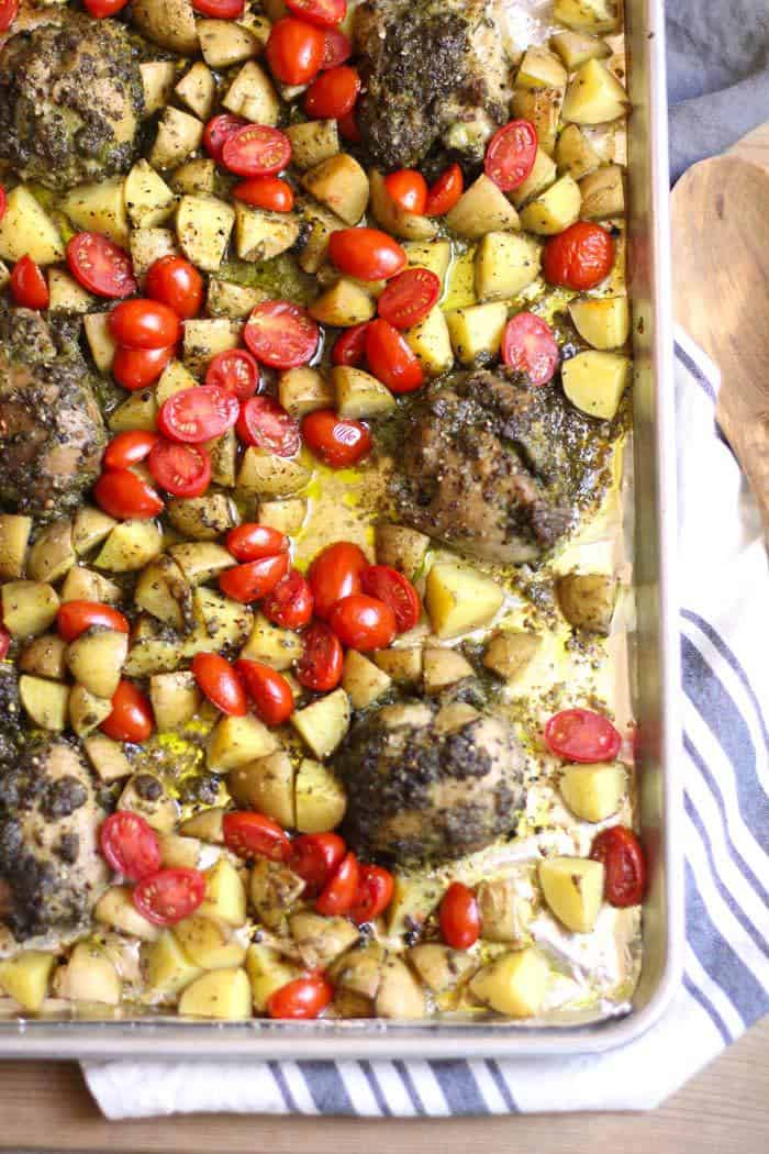 Overhead shot of one fourth of the sheet pan of pesto chicken, potatoes and tomatoes, on a white and gray napkin.