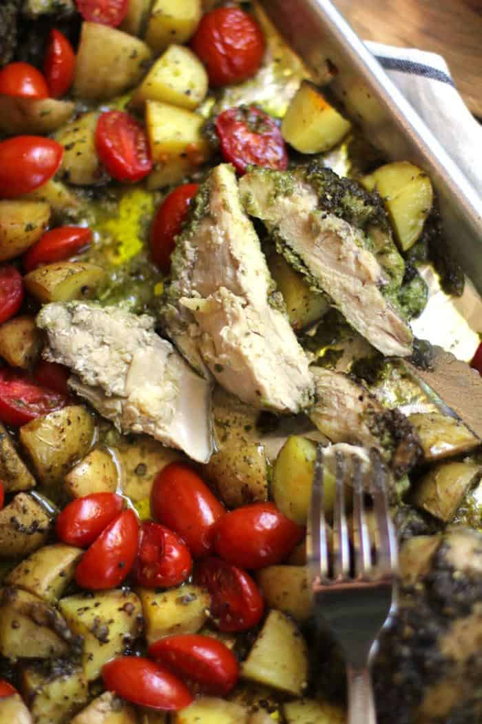 Close-up overhead shot of a sheet pan of pesto chicken, potatoes and tomatoes, with the chicken cut into pieces.