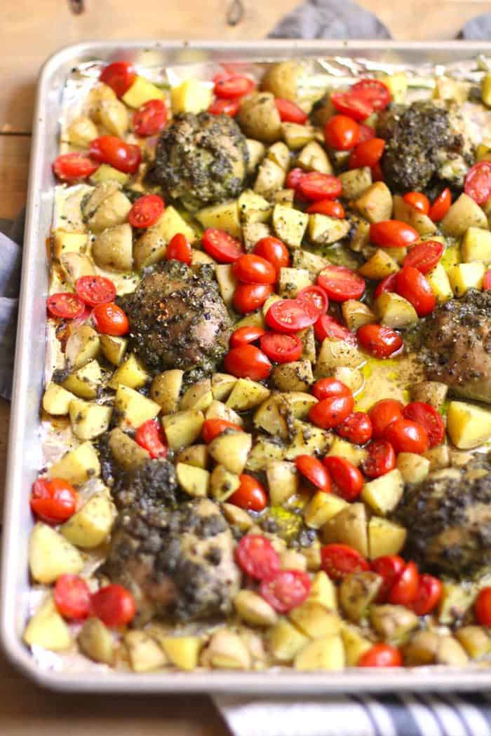 Side shot of a sheet pan of pesto chicken, potatoes and tomatoes, on a wooden background.