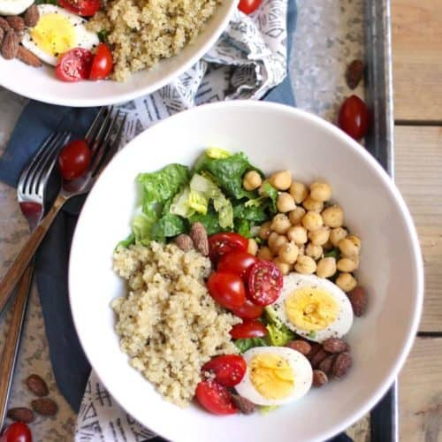 Overhead shot of two bowls of protein packed quinoa salad, on a gray tray.