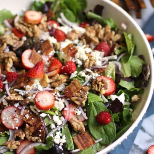 Overhead shot of a large white bowl of strawberry bacon salad with a jar of creamy strawberry dressing beside it.