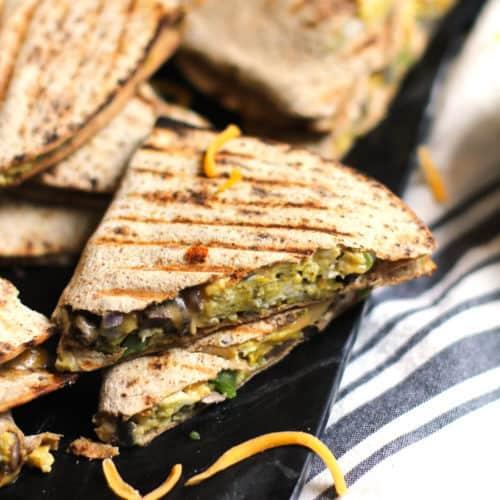 Side shot of a black platter of veggie omelette quesadillas.
