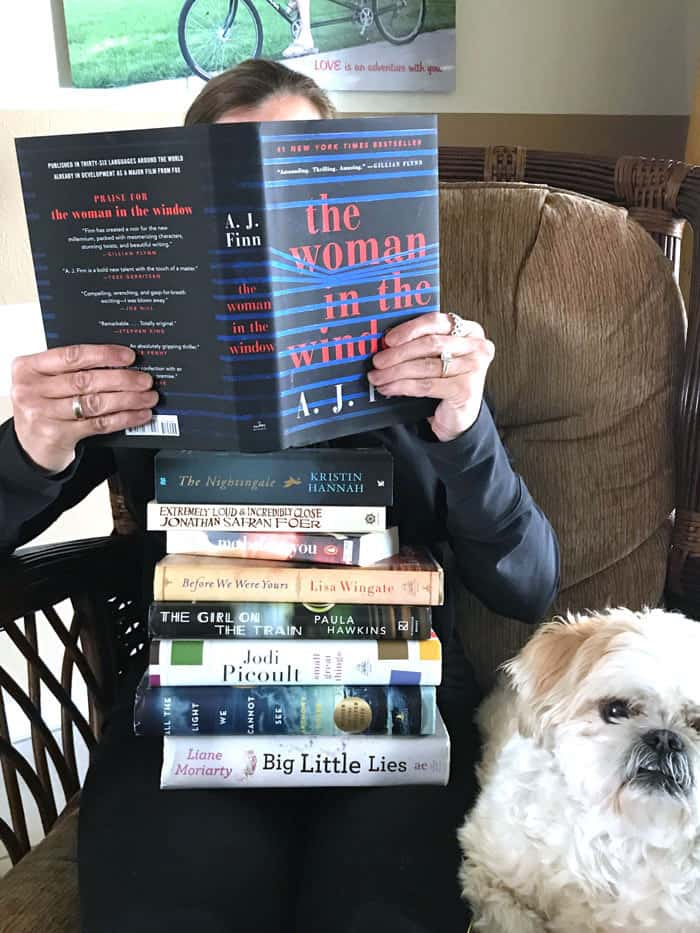 Me sitting on a chair with a stack of books and one open in front of my face, with my dog beside me.