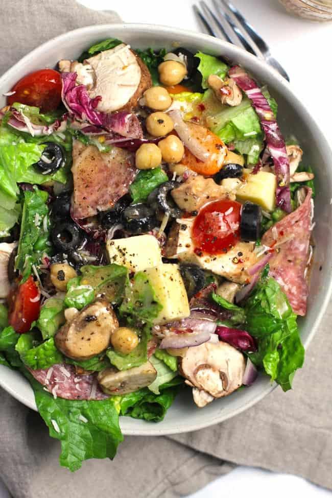 Overhead closeup shot of a white bowl of best Italian Chopped Salad, on a gray napkin.