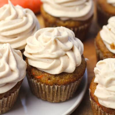 Overhead shot of several carrot cake cupcakes on a wooden board, with a small white plate, and whole carrots in the background.