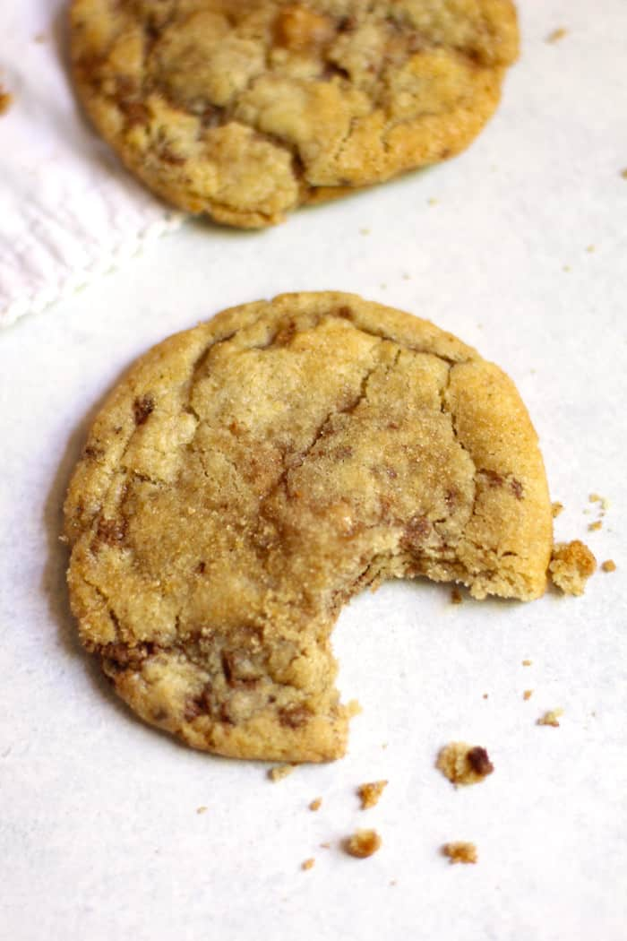 Overhead shot of a toffee cookie with a big bite missing, and crumbs, on a white background.