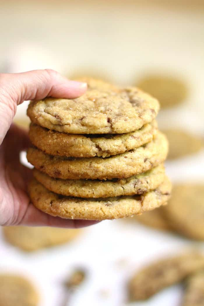 A side shot of my hand holding five stacked cookies, with other cookies in the background.