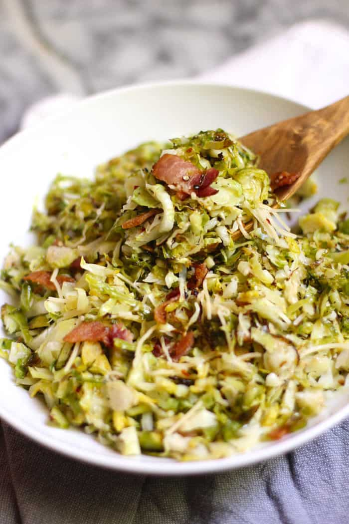 A side shot of a large white bowl filled with shaved Brussels sprouts and bacon, with a wooden spoon scooping some out, on a gray and white background.
