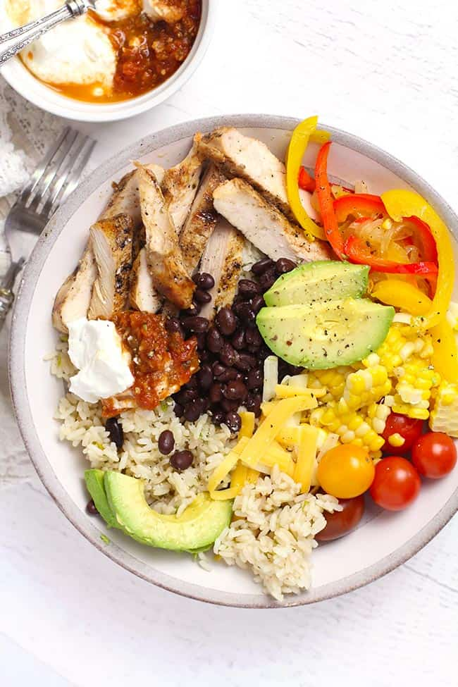 Overhead shot of a chicken burrito bowl with all the toppings, separated by ingredient.