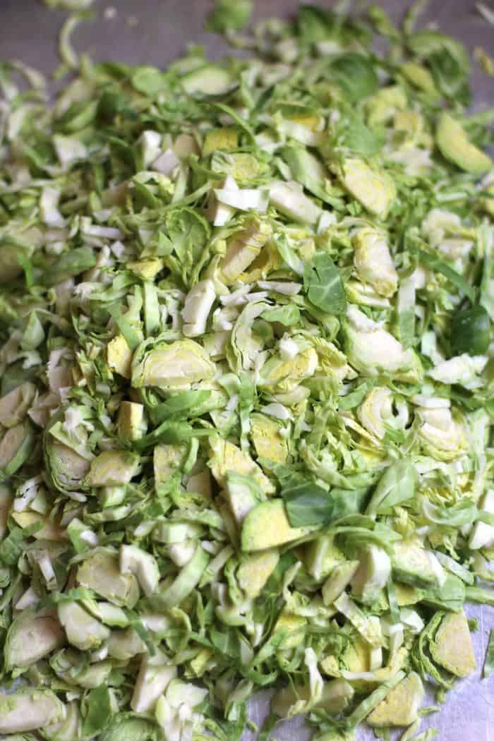 An overhead shot of a baking sheet of raw, shaved Brussel sprouts.
