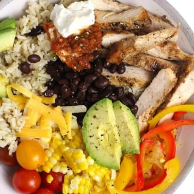 Closeup shot of a white bowl of chicken burrito bowl, with rice, black beans, onions, peppers, corn, tomatoes, cheese, and avocado slices.