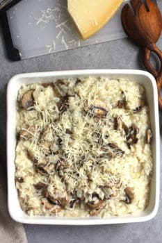 Overhead shot of a square dish of creamy mushroom risotto, with a wooden spoon and a parmesan cheese wedge.
