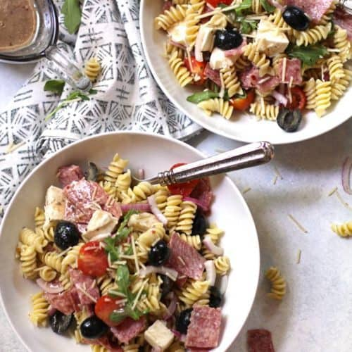 Two bowls of best Italian pasta salad, on a white background.