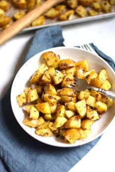 Overhead shot of mustard roasted potatoes in a shallow white bowl, placed on a blue napkin with a fork in the middle.