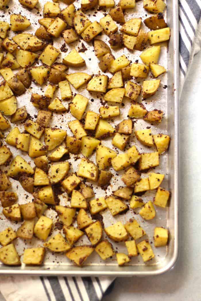 Overhead shot of a large corner of a sheet pan with mustard roasted potatoes.