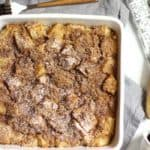 Overhead shot of French toast casserole in a square white dish, on a gray napkin and forks lying nearby.