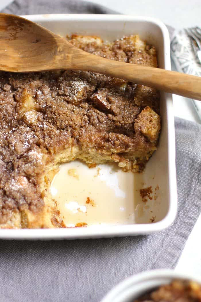 Overhead shot of French toast casserole in a square white dish, with a large serving gone in the lower right corner, on a gray napkin with a wooden spoon.