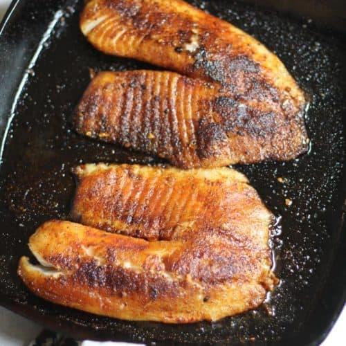 Overhead shot of a cast iron skillet with two pieces of blackened tilapia.