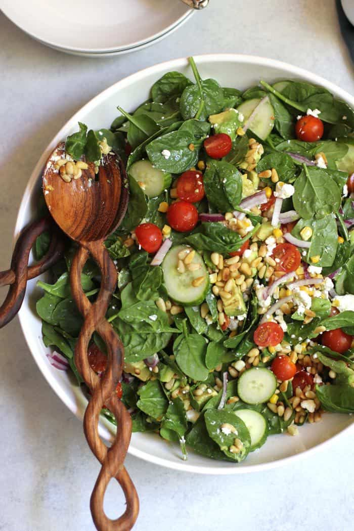 A large bowl of spinach salad with avocado and goat cheese and corn, with a wooden spoon.