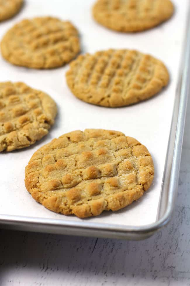 Side shot of a baking sheet of baked peanut butter cookies, on white parchment paper.