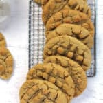 Overhead shot of a row of peanut butter cookies on a wire rack, on a white background.