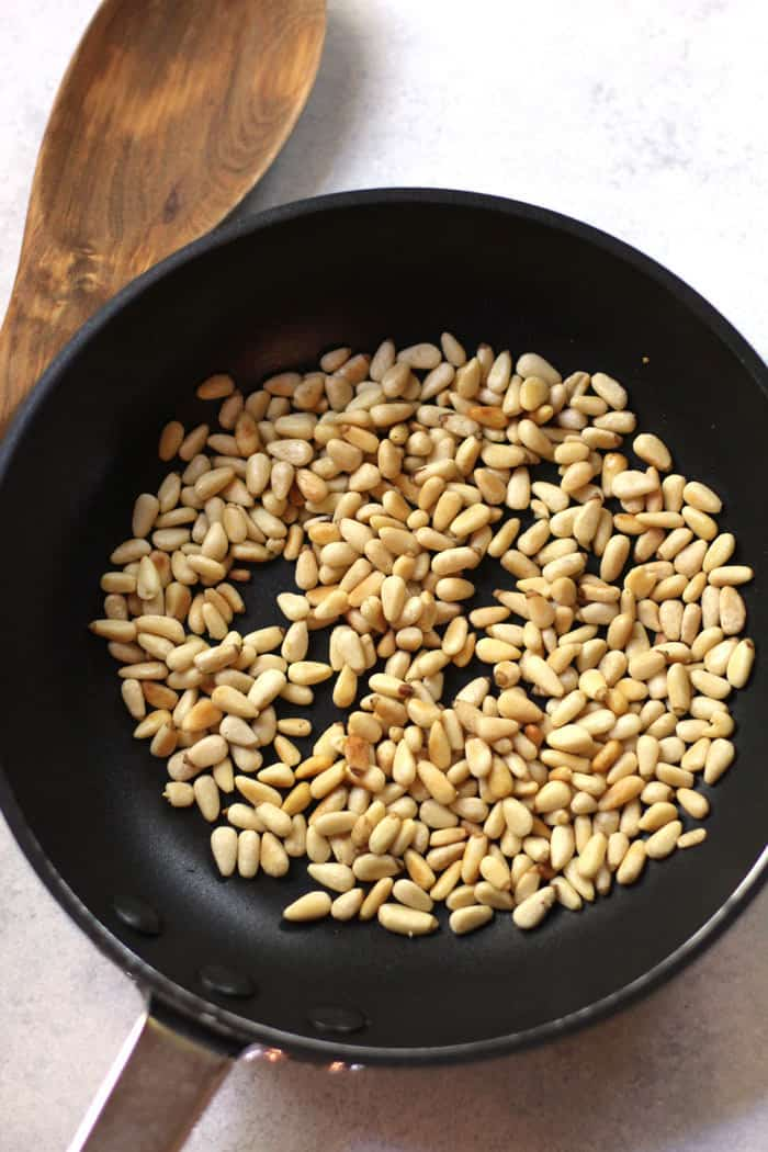 A small skillet with toasted pine nuts inside, alongside a wooden spoon, on a white background.