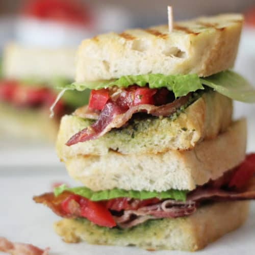 A double stack of BLT pesto sandwich on a white surface.