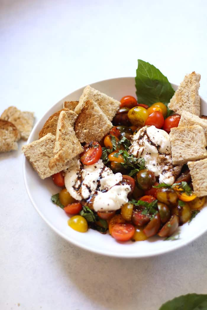 A white bowl of balsamic glazed tomatoes and burrata, with bread.