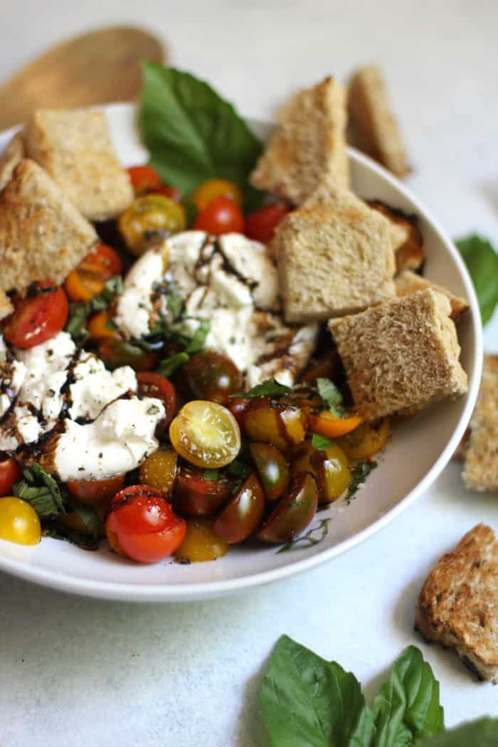 Closeup of a white bowl of balsamic glazed tomatoes and burrata, with bread.