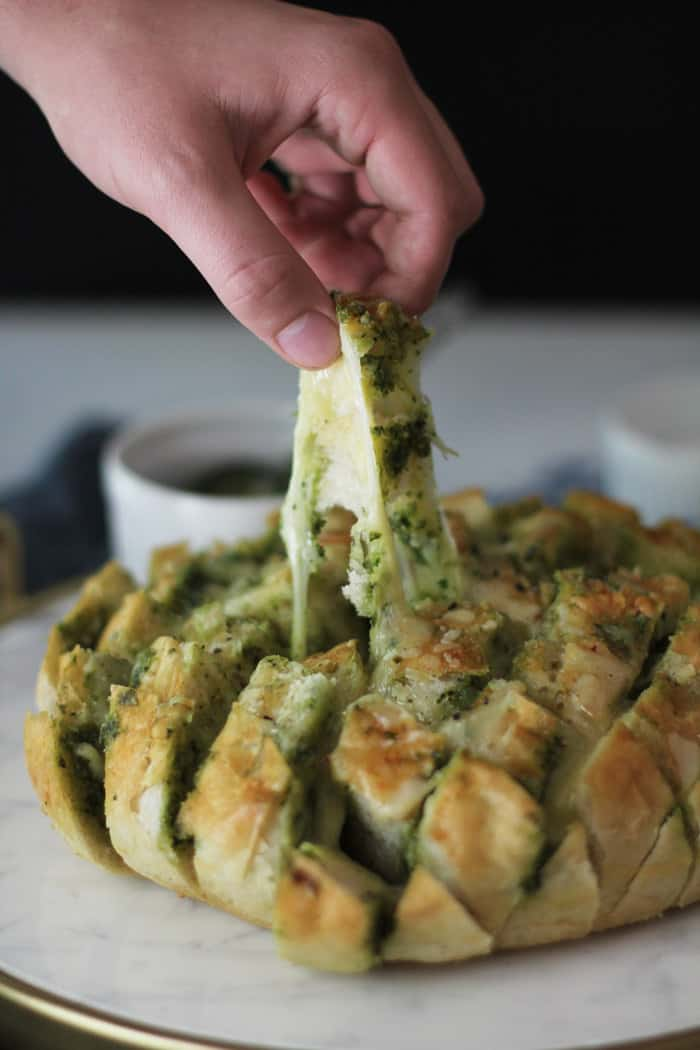 Side shot of a hand pulling a piece of cheesy bread from a loaf of Cheesy Pesto Party Bread.