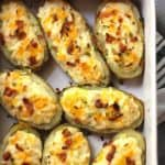 Overhead shot of twice baked potatoes in a rectangular white casserole dish, showing the lower left corner and the white handle.