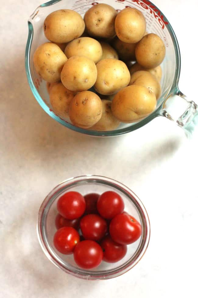 Overhead shot of a measuring glass cup of whole yellow baby potatoes, and a smaller glass bowl of cherry tomatoes.