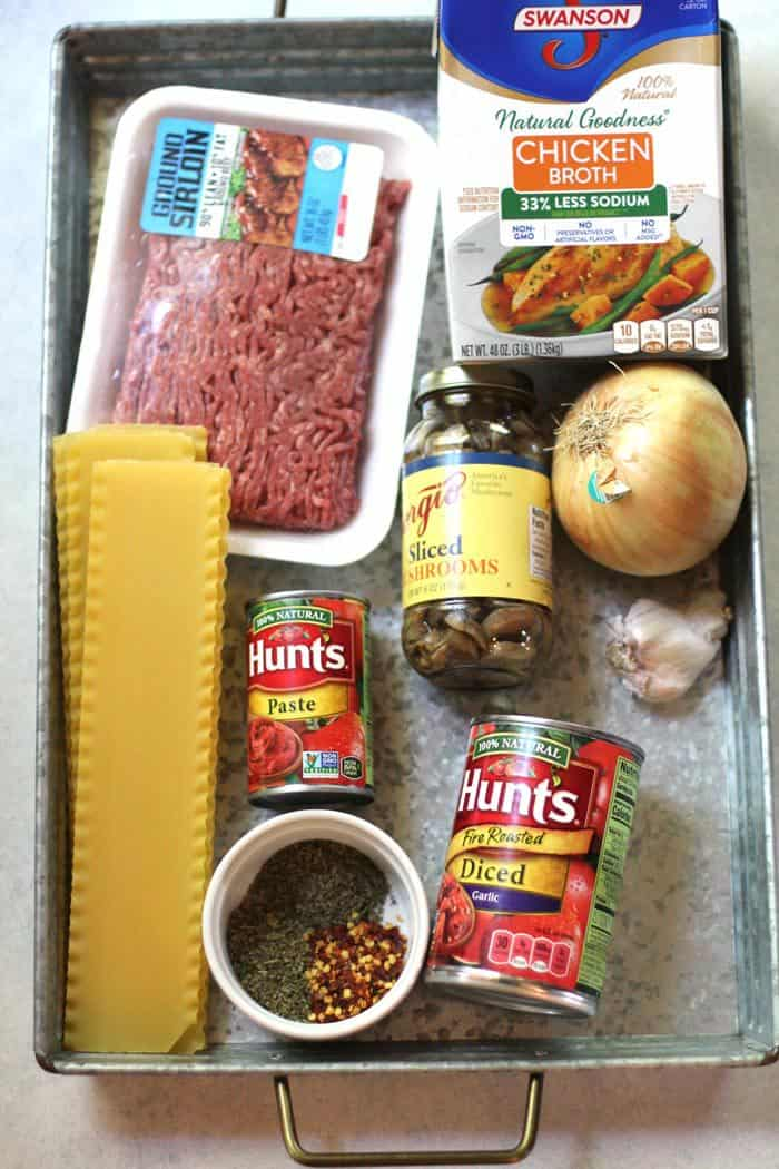 Overhead shot of lasagna soup ingredients all spread out on a gray tray with handles.