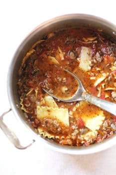 Overhead shot of a large sauce pan of lasagna soup, with a soup ladle inside, all on a white background.